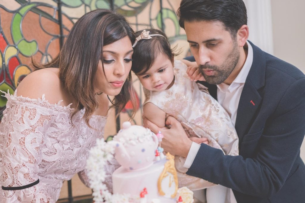 Melbourne family photography - Family blow out a first birthday cake.