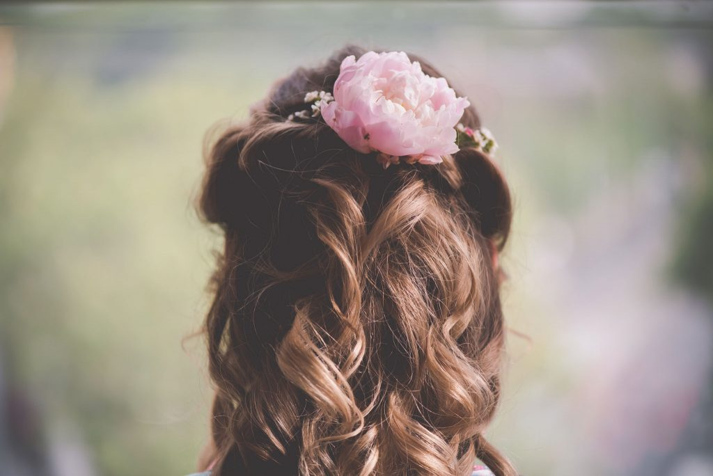 A bride shows off the pink flower in her hair. Melbourne wedding photography by pause the moment. Windsor hotel wedding photography