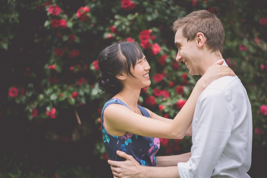 A couple laugh at a Spring engagement photography session in Melbourne