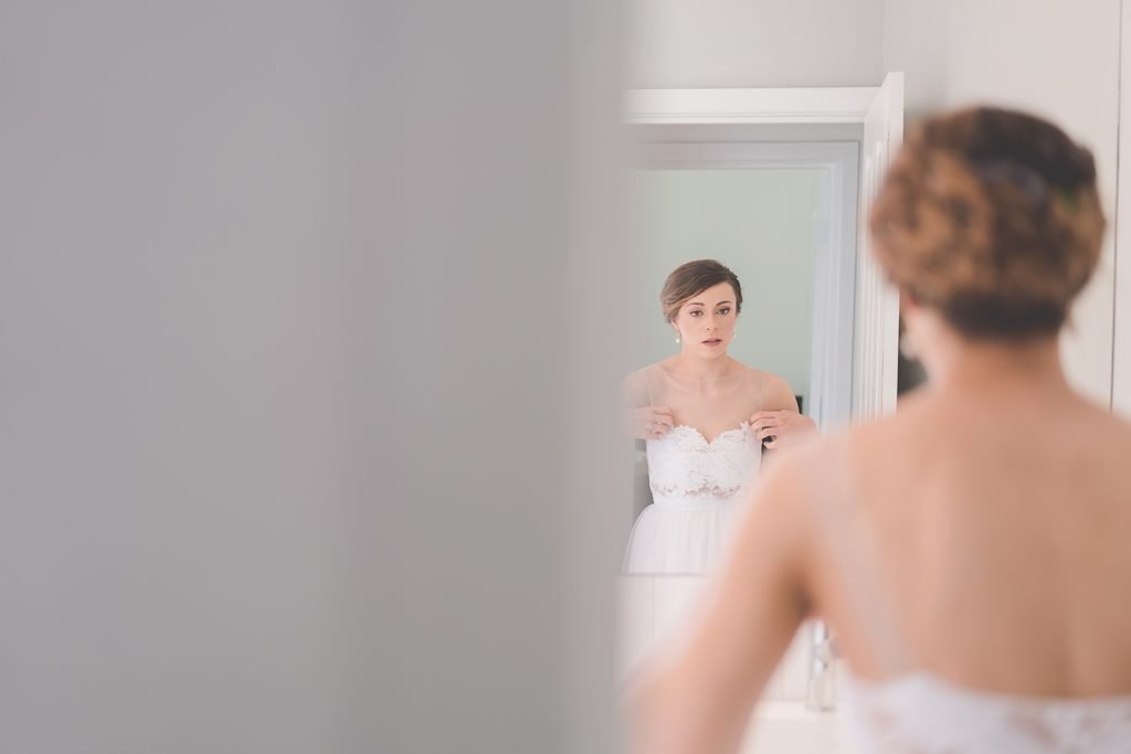A nervous bride adjust her dress in front of a mirror.