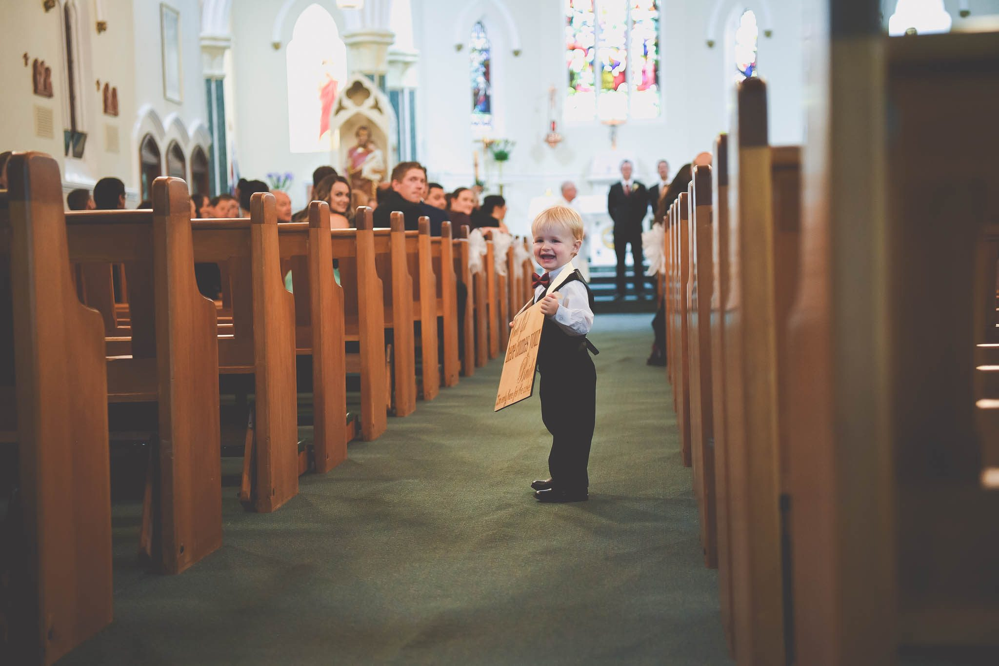 Cute photograph of the bride's nephew as he walks down the aisle with a sign at a Melbourne wedding