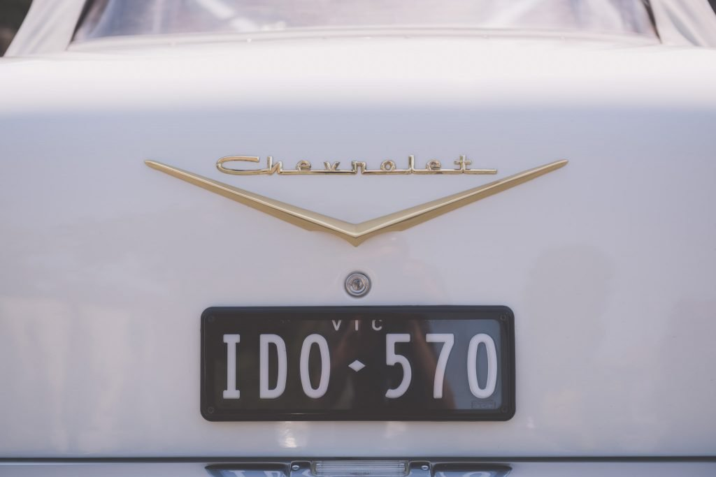 """The back of a white Chevrolet Bel Air with the Number Plate """"I DO"""". These cars are very popular for Melbourne wedding photography."""