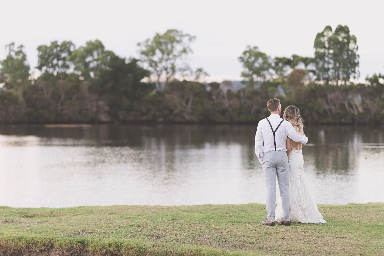 Beautiful photo of Laura and Mitch standing by a lake holding each other on their wedding day.