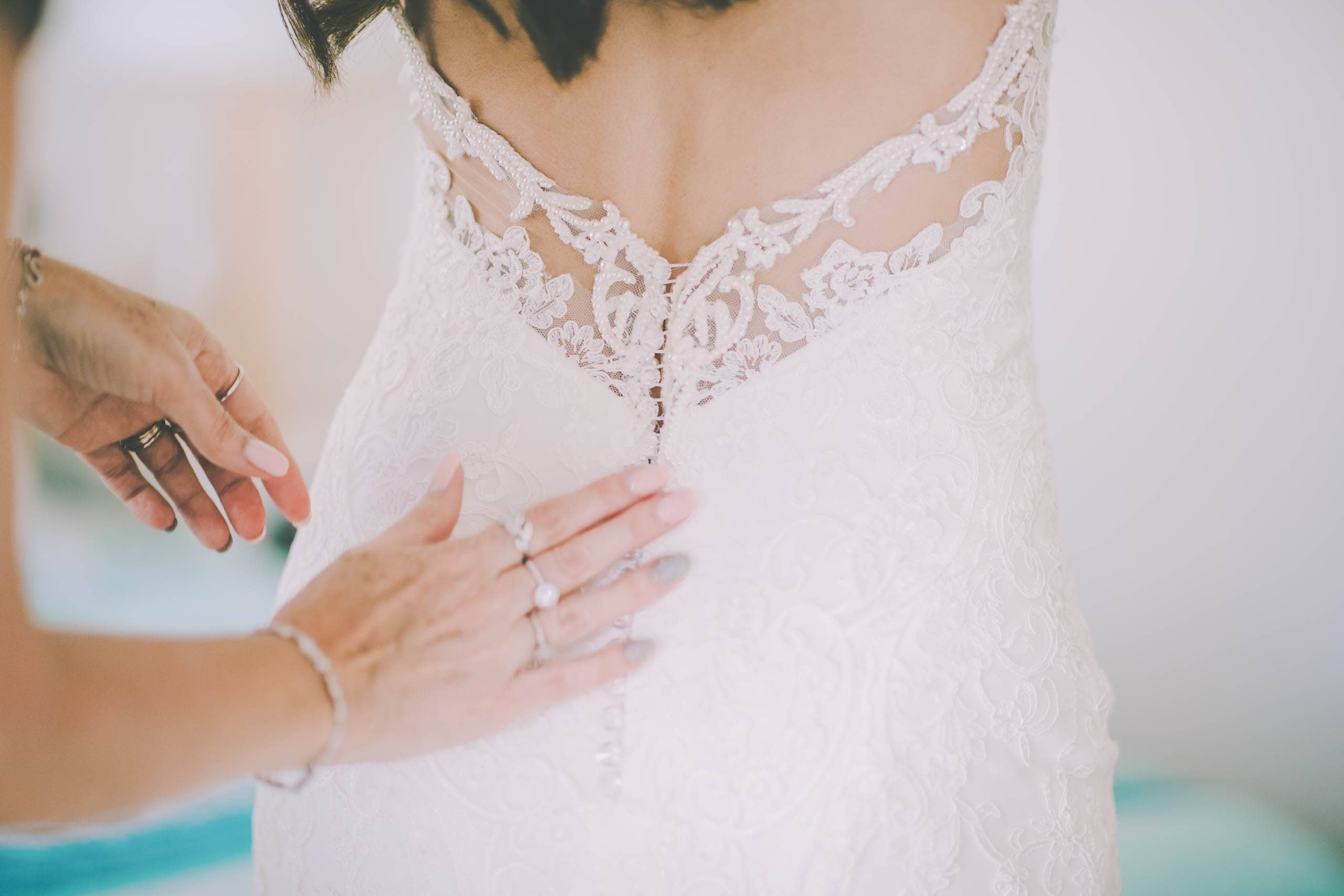A bride has her dress done up before her Sorrento beach wedding